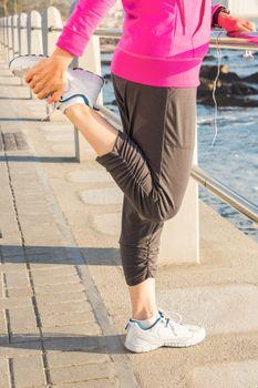 Sporty woman stretching leg at promenade