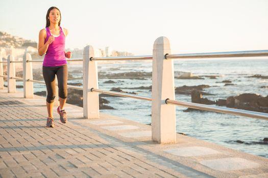 Fit woman jogging at promenade