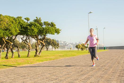Focused sporty blonde jogging at promenade