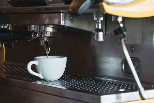 A coffee cup with coffee machine in coffee shop.