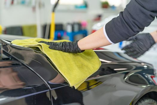 polishing the body of luxury cars with the help of a microfiber cloth for a perfect shine