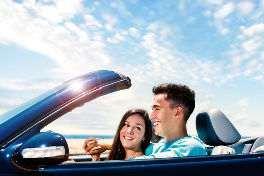 Close up portrait of Happy young couple driving blue convertible along seaside.
