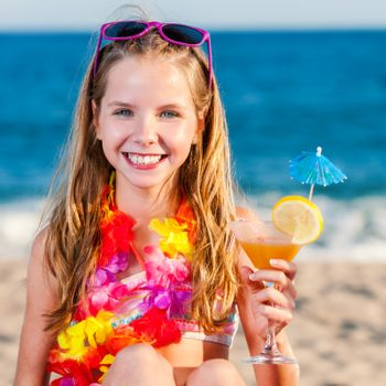 Close up portrait of attractive little preteen girl on beach holding fruit cocktail.