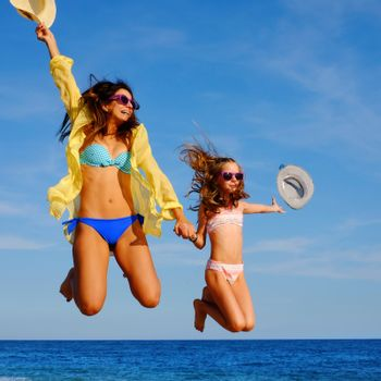 Close up action portrait of young girls on holiday jumping on beach. Two attractive happy women in bikini and sunglasses throwing hats in air.