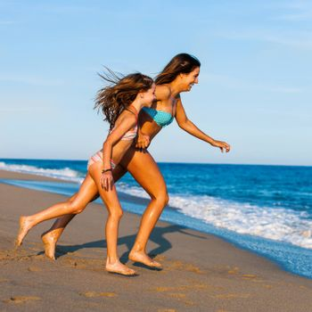 Action portrait of Young Mother running with daughter on beach.Two young girls in swimwear running to water.