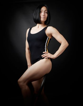 young woman in a black bodysuit posing on a dark background