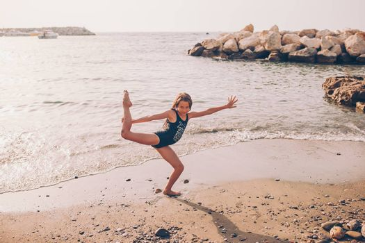 Little girl having fun at tropical beach during summer vacation playing together at shallow water. Cute kid making sporty exercises on the seashore