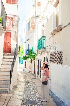 Girl tourist walks outdoors in narrow street