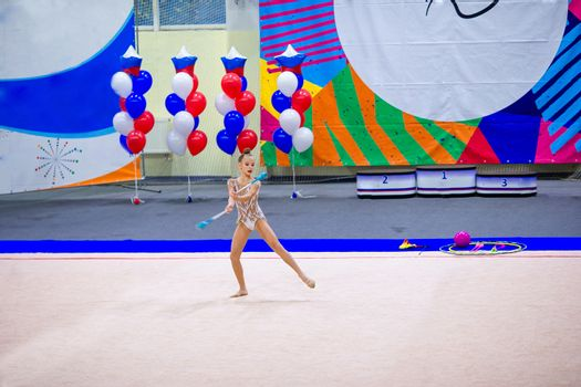 Beautiful little gymnast girl with her performance with maces on the carpet on competition
