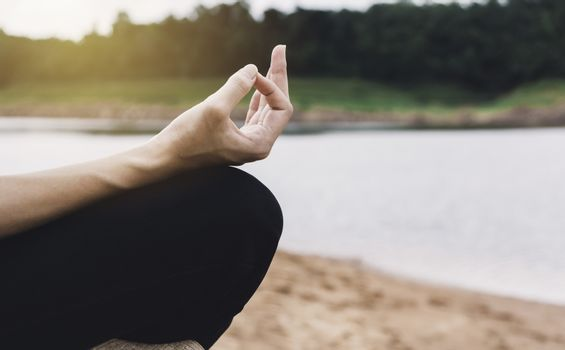 Woman meditating at near river for lifestyle relaxation emotional concept.