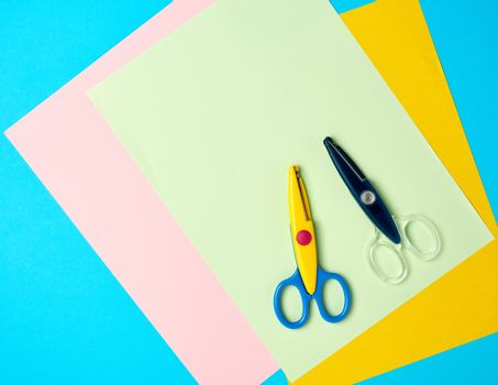 pair of plastic scissors and colored paper on a blue background, back to school backdrop