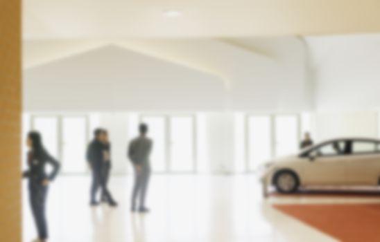 People at the cars showroom blurred background. blurred showroom