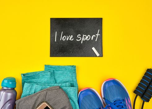 empty blackboard and blue women's sneakers and clothes for sports on a yellow  background, top view, copy space, flat lay