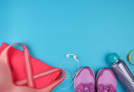 pink women's sneakers, bottle of water, clothes and bras for sports on a  blue background, top view, copy space