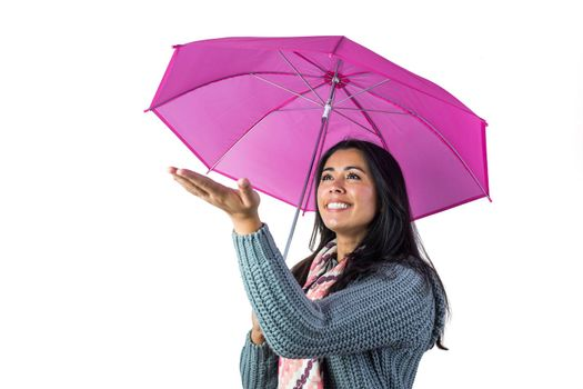 Woman checking the weather from under her umbrella against a white background