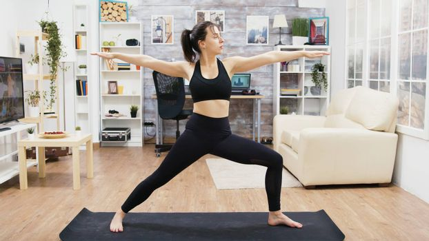 Calm young female practicing yoga exercises in living room. Healthy lifestyle.