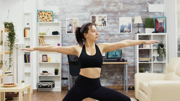 Young woman keeping her eyes closed standing in yoga pose. Woman keeping a healthy lifestyle.