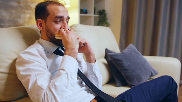 Businessman in formal wear sitting on couch eating a burger