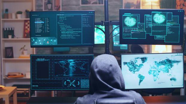 Back view of cyber terrorist using supercomputer