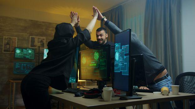 Team of cyber criminals celebrate after a successful hack