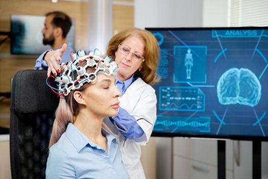 Doctor arranging neurology scanning headset for tests on a femal