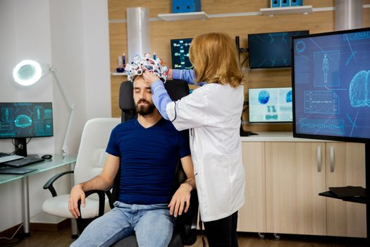Doctor putting brainwaves scanning headset on male patient