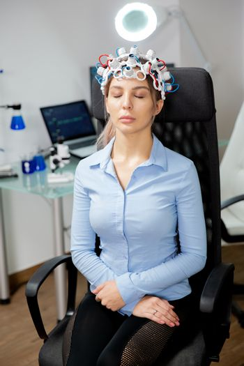 Female patient with brain waves scanning device in neurology lab