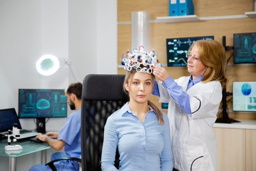 Doctor arranging brain waves scanning headset for a patient
