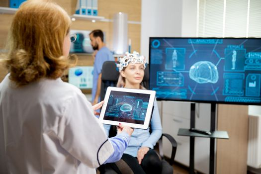 Doctor who looks at the evolution of the patient's brain on the tablet