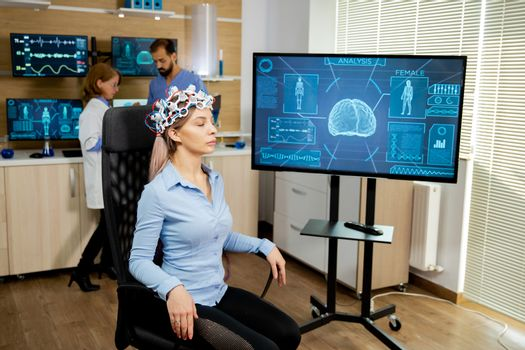 Patient woman with head scanning device and brain activity is seen on screen