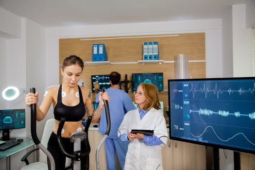 Female athlete doing physical effort on stepper and doctor with