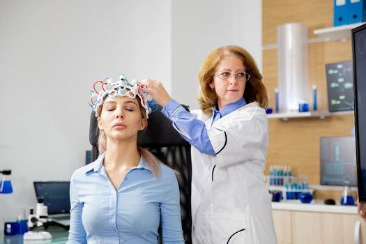Doctor adjusting brain waves scanning device on the patient's he