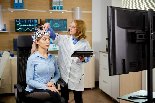 Patient woman with brain waves scanning device adjusted by docto