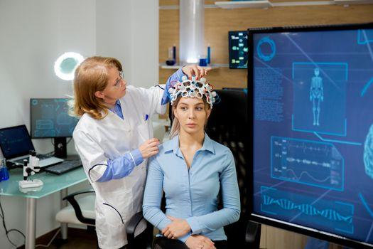 Doctor adapting neurology helmet during a brain scan procedure