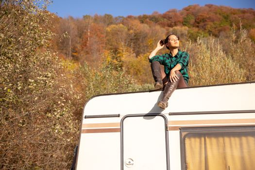 Young girl relaxing on the roof of a retro camper in a fall nightmare