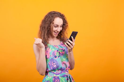 Young woman looking with excitement at her phone