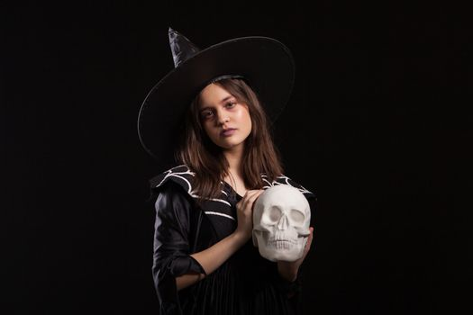 Portrait of little girl dosing dark sorcery with a human skull at halloween carnival