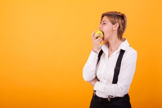 Pretty woman with casual clothes taking a big bite from a green apple over yellow background. Beautiful woman eating a green apple.