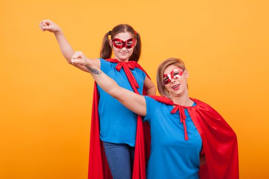 Beautiful mother and her little daughter dressed like superheros are keeping one hand up over yellow background