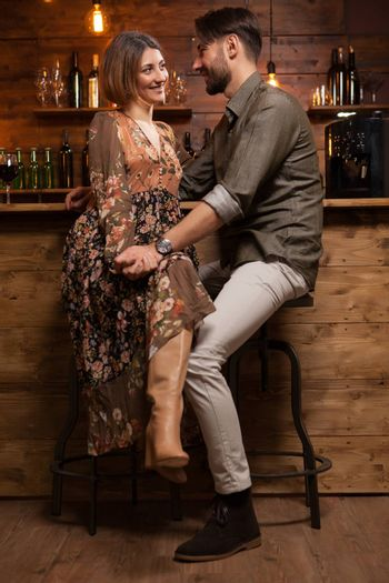 Stylish young couple on a night out in a vintage pub and holding hands. Looking into each others eyes.