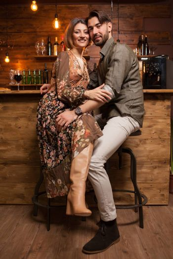 Beautiful young couple sitting at the counter and smiling to the camera. Stylish couple. Coxy atmosphere. Vintage pub.
