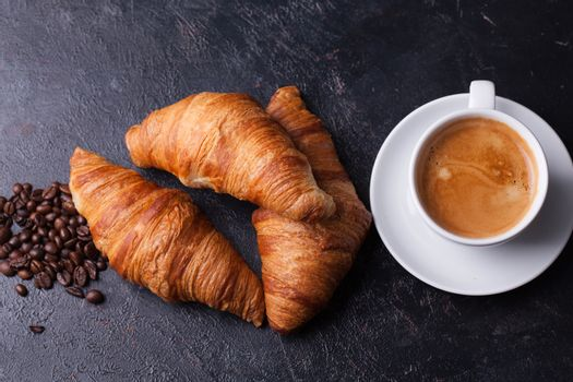 Croissants with mug of coffee and coffee beans on dark wooden table. Delicious desserts