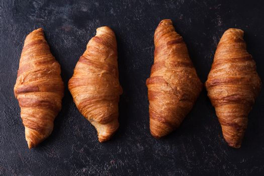Fresh baked traditional croissants on dark wooden table. Morning snack.