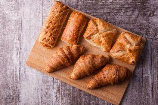 An assortment of freshly baked pastry aligned on cutting board. Delicious dessert.