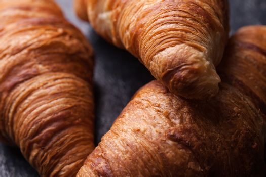 Tasty french croissants on a black wooden table. Great dessert