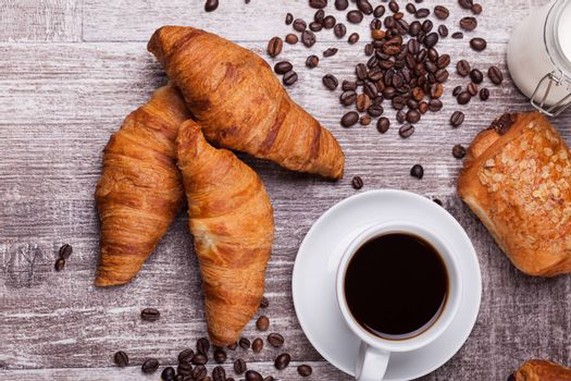 Coffee and freshly baked butter croissant on vintage wooden table. Delicous brunch.