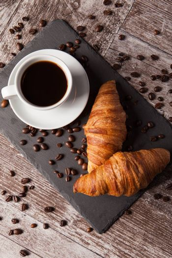 Cup of coffee and spreaded coffee beans with fresh croissants. Delicous dessert.