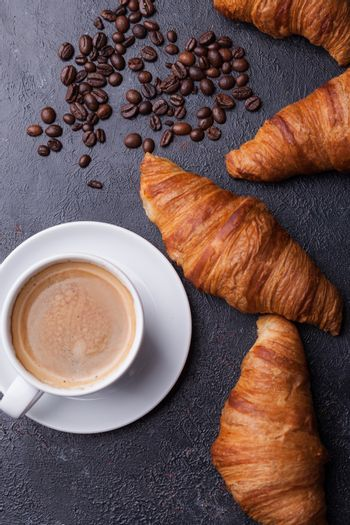 Top view of coffee and croissant with coffee beans. Delicous coffee.