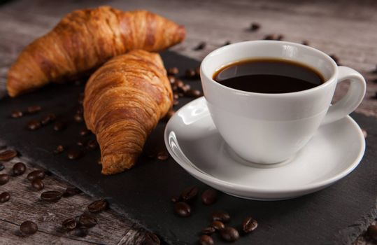 Mug of coffee with delicious pastry and spreaded beans of coffee. Morning snack.