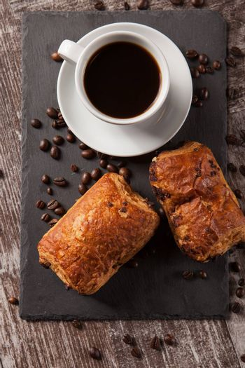 Mug of coffee with delicious pastry and spreaded beans of coffee. Fresly baked.
